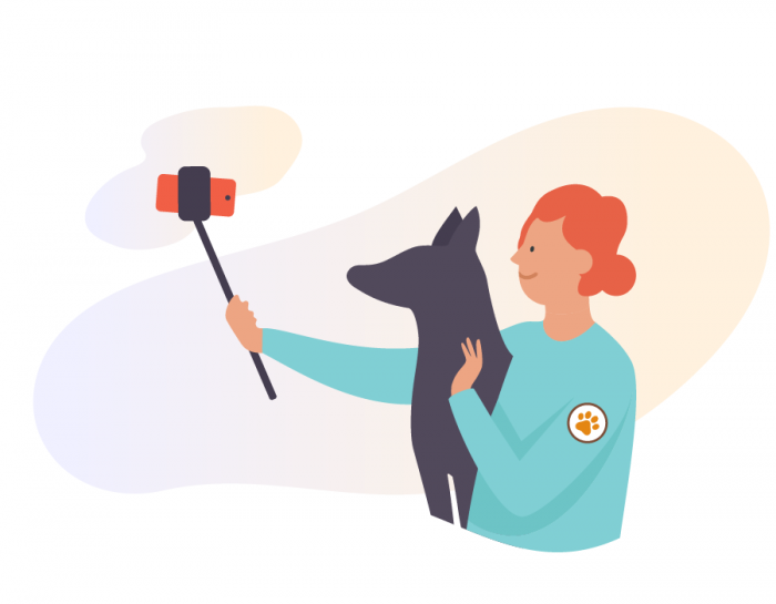 An animal shelter owner taking a selfie with a rescued dog