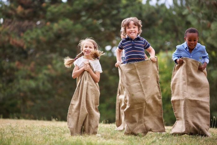 Children competing at sack race and having fun