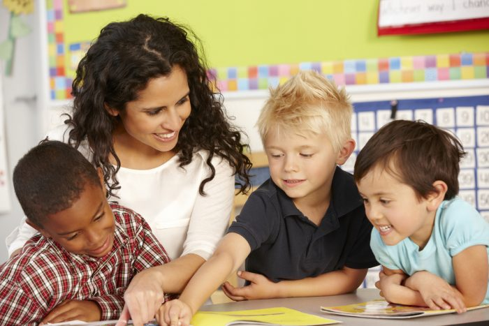 teacher with students coaches them in their individual learning plans