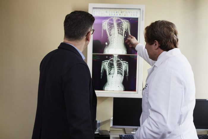 Two people looking at PHI in the form of x-rays