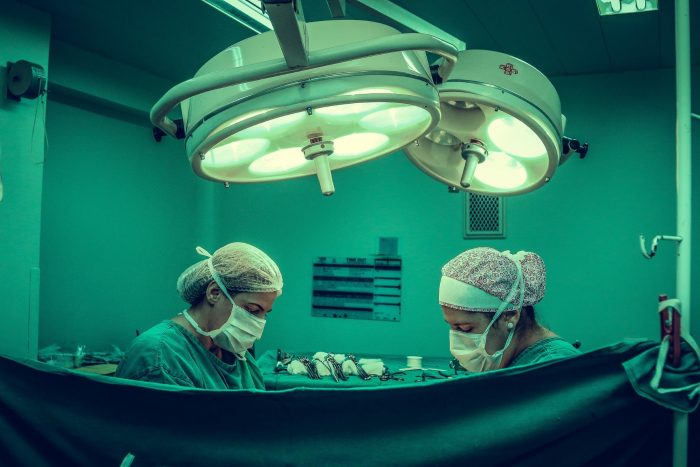 Two healthcare workers performing surgery have a partition up to maintain patient privacy.