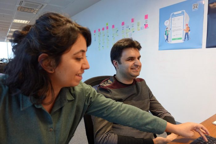 A photo of user researcher Gokce and Cagri having a usability test next to a white wall with post-its and posters on it.