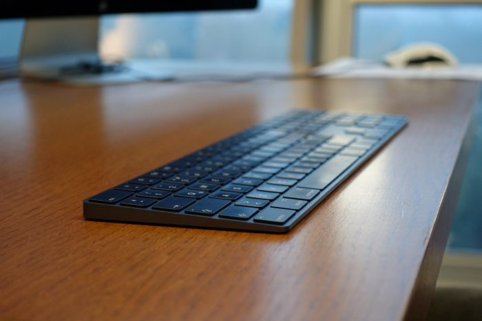 A close-up photo of a black iMac keyboard on a wooden table.