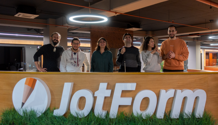 A photo of five user researchers and Cagrı over a JotForm logo at the entrance of JotForm Ankara office.