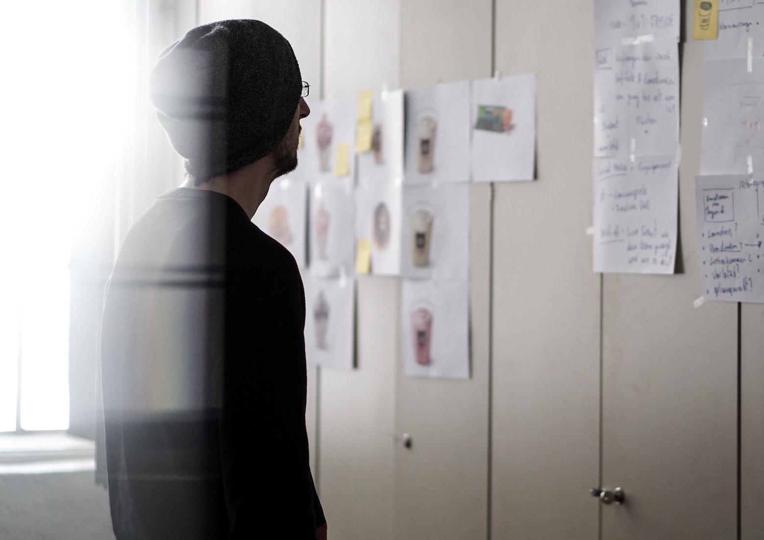 man looking at flowcharts at the board