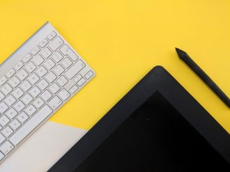 a keyboard and a tablet on a yellow background