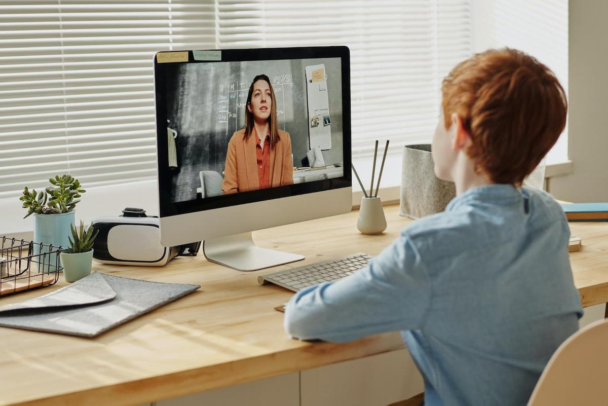 A teacher uses video conferencing to help a student.