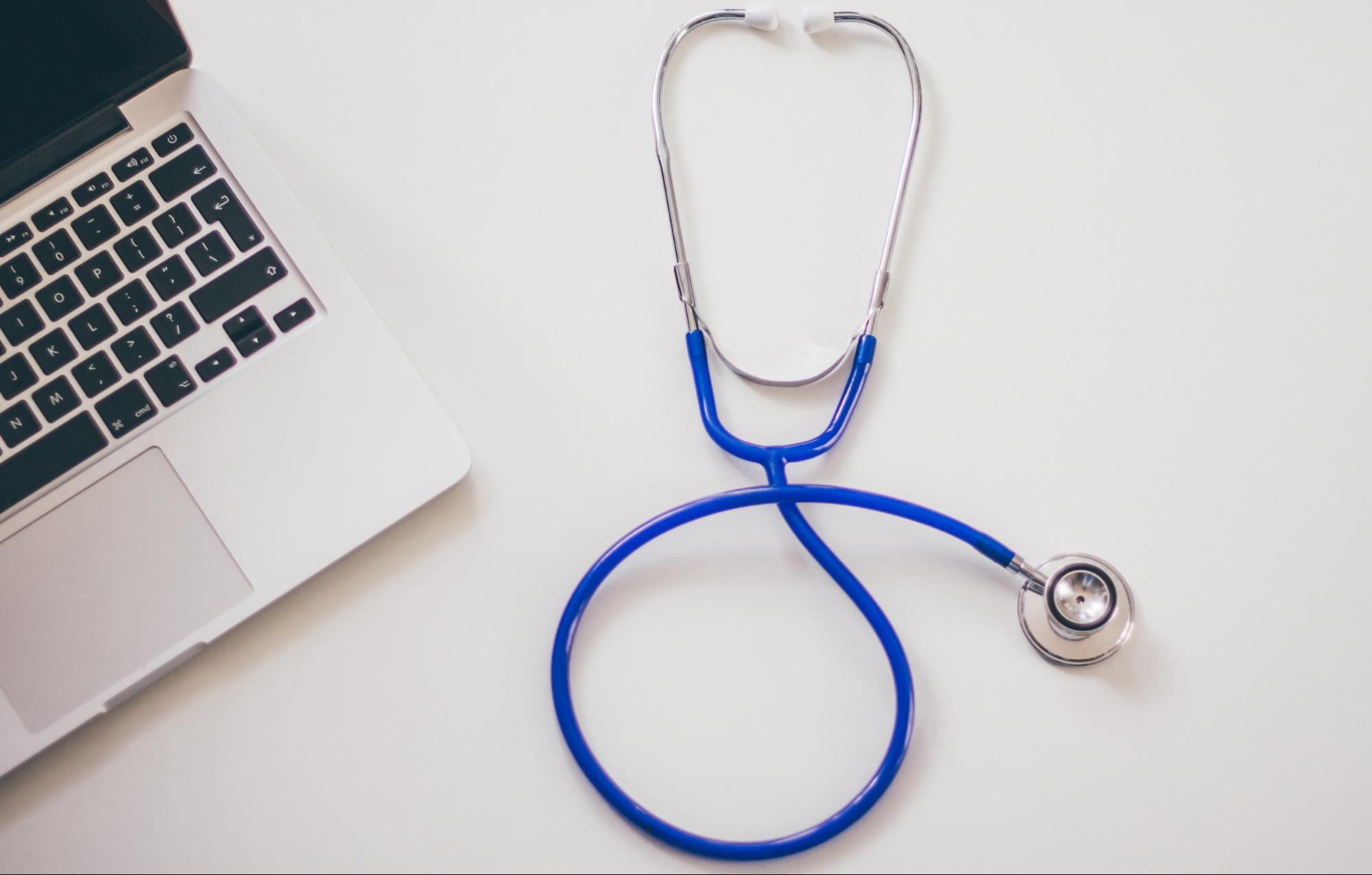 A blue stethoscope on a table next to a laptop