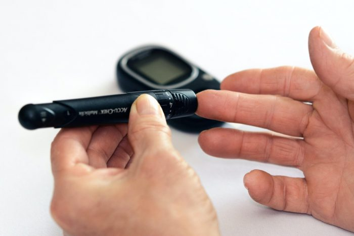 A patient uses a remote blood glucose monitor to keep track of their health.