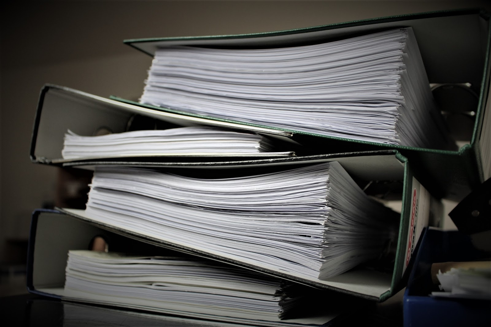 A stack of files sits in binders on a table.
