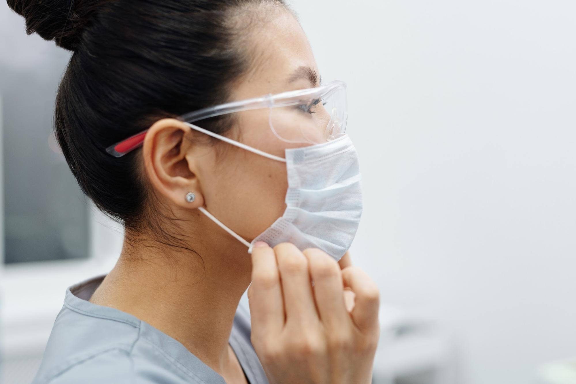 A healthcare employee puts on personal protective equipment.